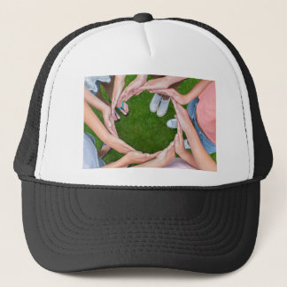 Many arms of children with hands making circle trucker hat