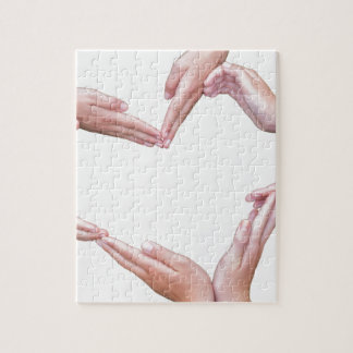 Many arms of girls construct heart on white jigsaw puzzle