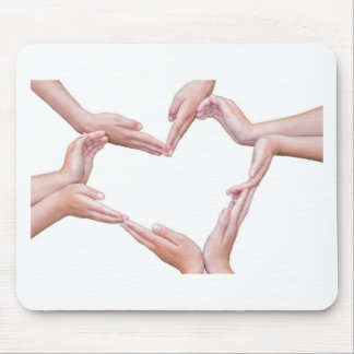 Many arms of girls construct heart on white mouse pad