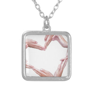 Many arms of girls construct heart on white silver plated necklace