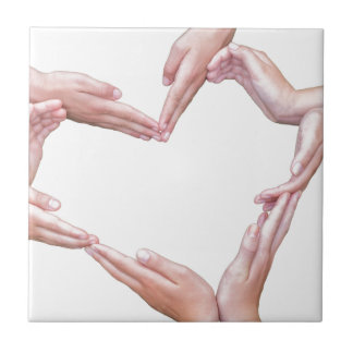 Many arms of girls construct heart on white tile