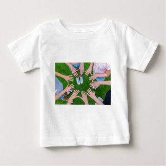 Many children hands joining in circle above grass baby T-Shirt