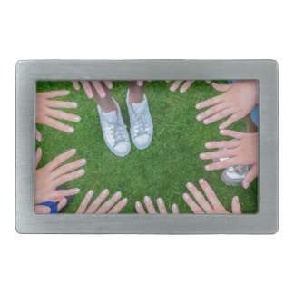 Many children hands joining in circle above grass belt buckle