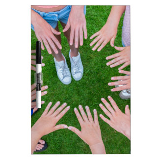 Many children hands joining in circle above grass dry erase board