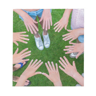 Many children hands joining in circle above grass notepad