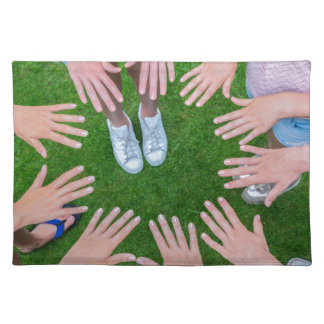 Many children hands joining in circle above grass placemat