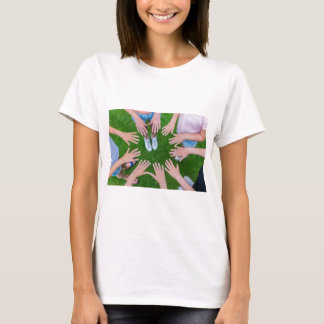 Many children hands joining in circle above grass T-Shirt