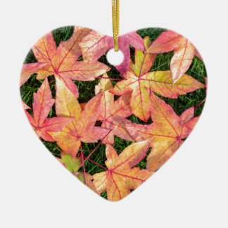Many colorful autumn maple leaves on green grass ceramic heart ornament