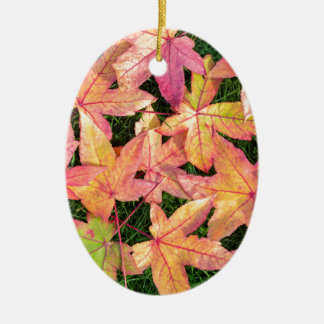 Many colorful autumn maple leaves on green grass ceramic oval ornament