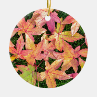 Many colorful autumn maple leaves on green grass round ceramic ornament