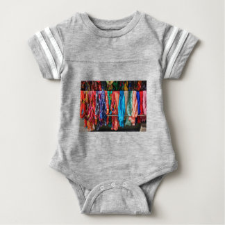 Many colorful scarves hanging at market baby bodysuit