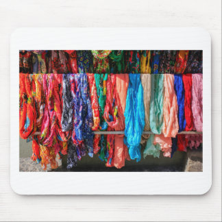 Many colorful scarves hanging at market mouse pad
