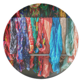 Many colorful scarves hanging at market plate