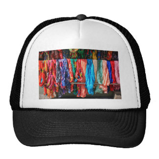 Many colorful scarves hanging at market trucker hat