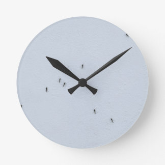 Many mosquitoes on a wall round clock