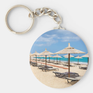 Many reed beach umbrellas in a row  on empty beach basic round button keychain