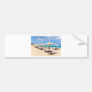 Many reed beach umbrellas in a row  on empty beach bumper sticker