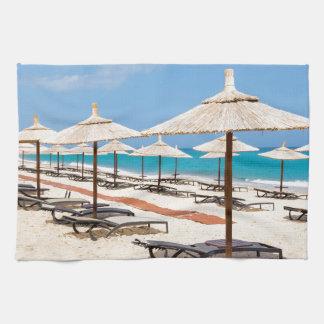 Many reed beach umbrellas in a row  on empty beach hand towel