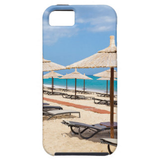 Many reed beach umbrellas in a row  on empty beach iPhone 5 case
