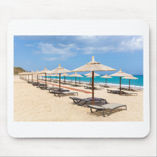 Many reed beach umbrellas in a row  on empty beach mouse pad