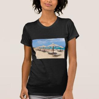 Many reed beach umbrellas in a row  on empty beach T-Shirt