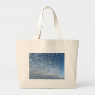 Many soft clouds against blue sky background large tote bag