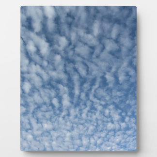 Many soft little clouds against sky background plaque