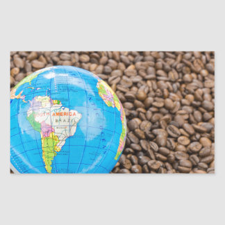 Many whole coffee beans with South America globe