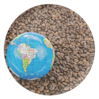 Many whole coffee beans with South America globe Plates