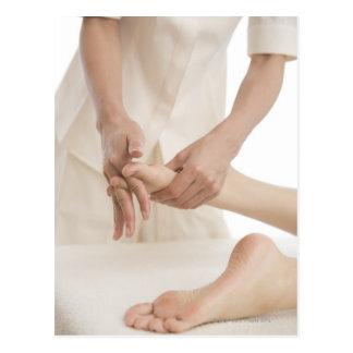 Massage therapist applying foot massage 2 postcard