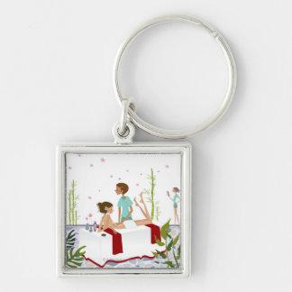 Massage therapist massaging a woman lying on a keychains