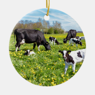 Meadow full of dandelions with grazing cows round ceramic ornament