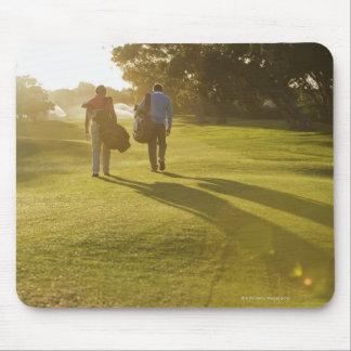 Men carrying golf bags on golf course mouse pad