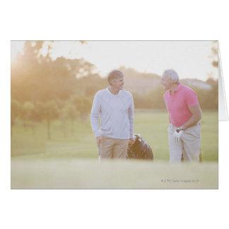 Men pulling golf carts card