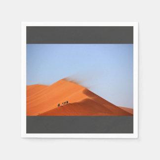 Men standing on sand dune in desert disposable napkins
