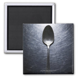Metal spoon on stainless steel square magnet