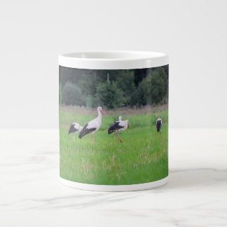 Migrating white storks, ciconia, in a meadow large coffee mug