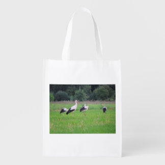 Migrating white storks, ciconia, in a meadow reusable grocery bag