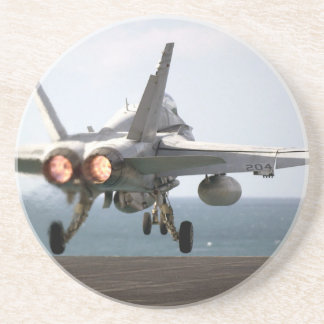 Military aircraft launching off aircraft carrier coasters
