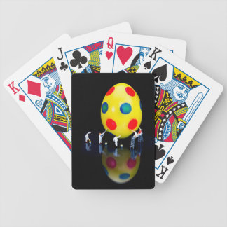 Miniature figurines painting yellow easter egg bicycle playing cards