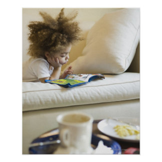 Mixed race boy reading book on sofa poster