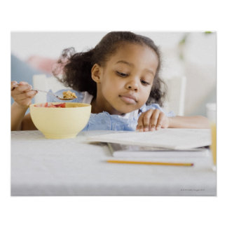 Mixed race girl reading and eating breakfast poster
