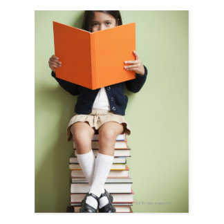 Mixed race girl sitting on stack of books postcard
