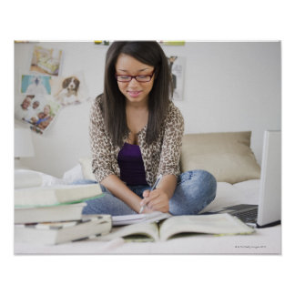 Mixed race teenage girl doing homework on bed poster