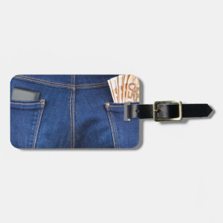 Mobile phone and euro money in blue jeans luggage tag