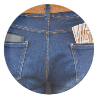 Mobile phone and euro money in blue jeans plate