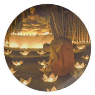 Moines allumant les bougies et les lanternes loy d assiette pour soirée