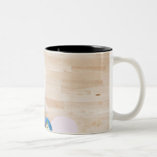 mongrel sitting in front of two bowls with dog Two-Tone coffee mug