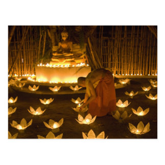 Monks lighting khom loy candles and lanterns for postcard