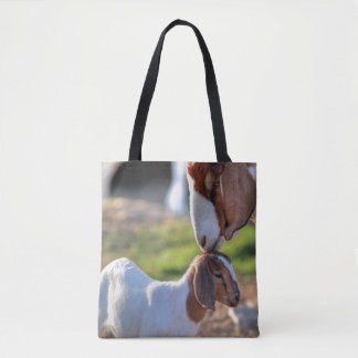 Mother goat kissing her baby on head. tote bag